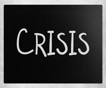 """Stock Photo of """"Crisis"""" handwritten with white chalk on a blackboard"""
