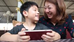 Happy asian boy and his mom playing games on smart phone - stock footage