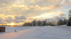 4K beautiful snowy cloudy sunset with kids sledding and cars going slow Stock Footage