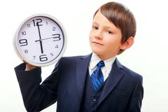 Business child in suit and tie posing with clock - stock photo