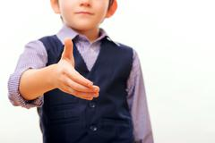 Cute child in suit stretching out hand - stock photo