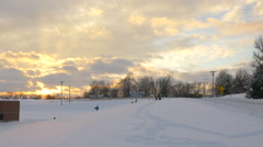 4K gorgeous golden sunset with kids playing in snow Stock Footage
