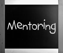 """The word """"Mentoring"""" handwritten with white chalk on a blackboar Stock Photos"""
