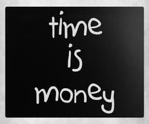 """Stock Photo of """"Time is money"""" handwritten with white chalk on a blackboard"""