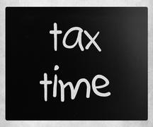 """""""Tax time"""" handwritten with white chalk on a blackboard Stock Photos"""