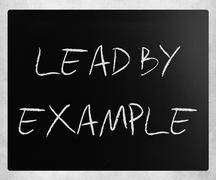 """""""Lead by example"""" handwritten with white chalk on a blackboard Stock Photos"""