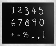 """Numbers"" handwritten with white chalk on a blackboard Stock Photos"