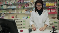 Stock Video Footage of Good looking pharmacist woman wrap with papers a medicine for the customer