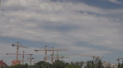 Background construction site with lots of tall cranes, lifting machines at work Stock Footage
