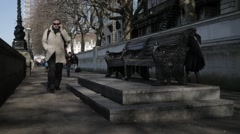 Pedestrians walk past bench on London's Southbank | HD 1080 Stock Footage