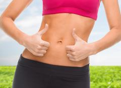 Close up of female abs and hands showing thumbs up Stock Photos