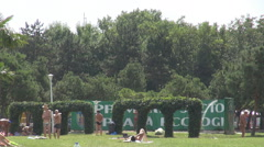 Men and women getting some tan, green space area, summer relaxation outdoors Stock Footage