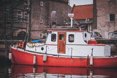 Stock Photo of small red  wooden motor boat tethered on the river dart