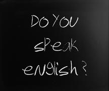 """""""Do you speak english"""" handwritten with white chalk on a blackbo Stock Photos"""