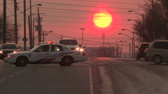 Sunset with police car cruiser blocking street at crime scene Stock Footage