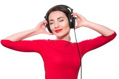 Attractive young adult woman in red clothes listening to the music touching b - stock photo