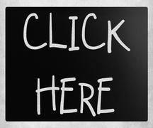 """""""Click here"""" handwritten with white chalk on a blackboard - stock photo"""