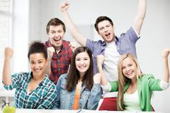 Students holding hands up at school Stock Photos