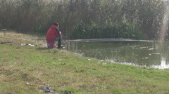 Old fisherman with many rods in water waiting fish catch, great hobby in nature Stock Footage