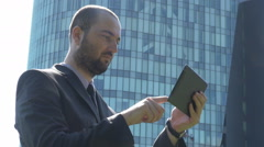 Focused serious young businessman work outside, tapping tablet screen, analyze Stock Footage