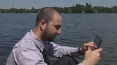 Lake shore background, businessman work with tablet, sliding tapping touchscreen Stock Footage