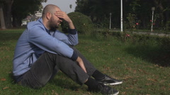Sad young man, single boy in the park, lovelorn depressed guy, endure hard alone - stock footage