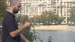 Man 20's slide and tap on mobile phone touchscreen in the city, cars motion view Stock Footage