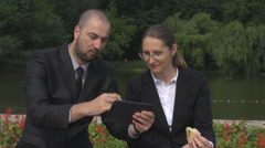 Business man and woman having a sandwich outdoors, working on tablet, sliding Stock Footage
