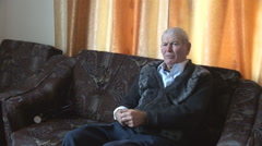 Old man home on sofa talking to the camera, senior left alone, loneliness, pain Stock Footage