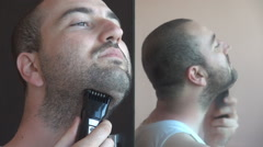 Cutting off black beard dry morning shaving man with electric trimmer and mirror Stock Footage
