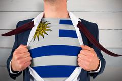 Composite image of businessman opening shirt to reveal uruguay flag Stock Photos