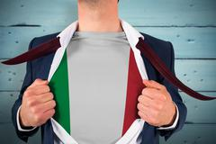 Composite image of businessman opening shirt to reveal italy flag Stock Photos