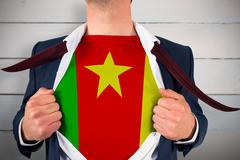 Composite image of businessman opening shirt to reveal cameroon flag Stock Photos