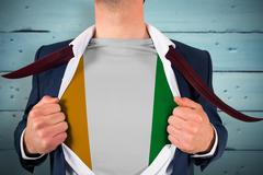 Composite image of businessman opening shirt to reveal ivory coast flag Stock Photos