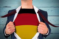 Composite image of businessman opening shirt to reveal germany flag Stock Photos