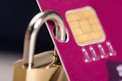 Closeup of padlock attached to credit card against black background Stock Photos