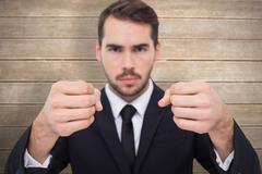 Composite image of exasperated businessman with clenched fists - stock photo
