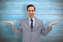 Composite image of smiling businessman presenting something with his hands Stock Photos