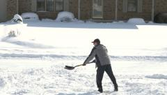 4K mature adult male shoveling snow at end of drive way Stock Footage