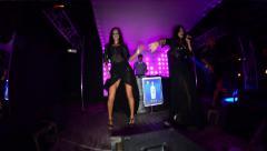 Singer sings a song. Beside her dance dancer. People dancing in nightclub Stock Footage
