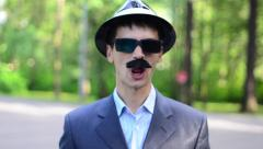 Man with a mustache, hat, sunglasses and a suit sing a song and grimaces - stock footage