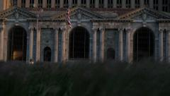 Rack focus from grass blowing in the wind to Michigan Central Station Stock Footage
