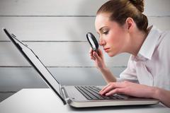 Composite image of attentive businesswoman typing on laptop - stock photo