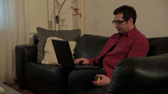 Man sitting on leather couch, typing on laptop and playing with ball. Leisure. Stock Footage