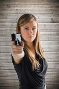 Composite image of femme fatale pointing gun at camera Stock Photos