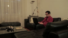 Man typing on laptop.Male writer sitting on couch and using computer for writing Stock Footage