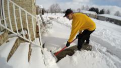 4K man clearing off deep snow front entrance to house Stock Footage