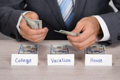 Midsection of businessman saving cash for college; vacation and house at tabl Stock Photos