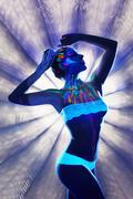 Unreal girl with luminous body art in spotlight Stock Photos