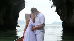 groom in white suit kiss his blonde bride - stock footage